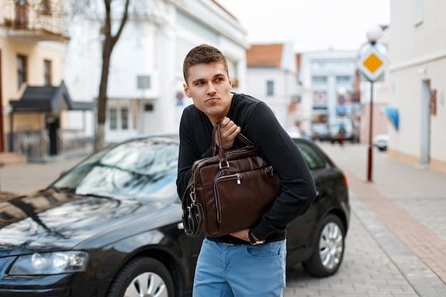 젊은 남자가 자동차 배경에 가죽 가방을 훔쳤다.