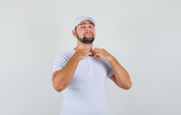 Giovane uomo che raddrizza il colletto in t-shirt, berretto e sembra pronto. vista frontale.
