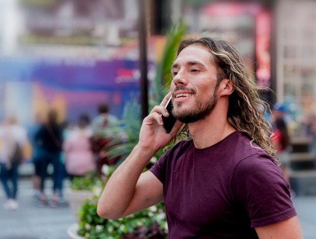 Young man on street talking over the phone