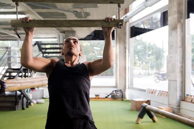 ジムでプルアップを行う若い男の筋力トレーニング
