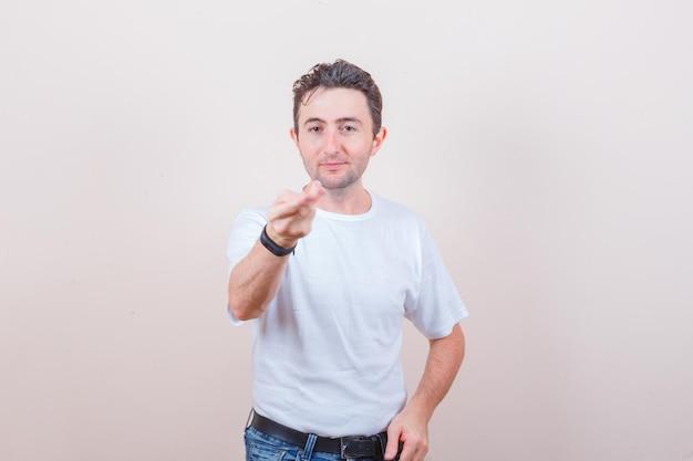 Молодой человек протягивает руку и пальцы в белой футболке, джинсах и выглядит уверенно