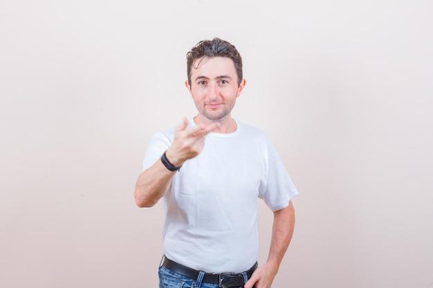 Молодой человек протягивает руку и пальцы в белой футболке, джинсах и выглядит уверенно Бесплатные Фотографии