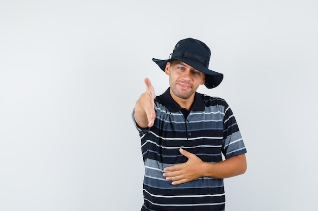 Молодой человек протягивает руку для тряски в футболке, шляпе и выглядит дружелюбно, вид спереди.