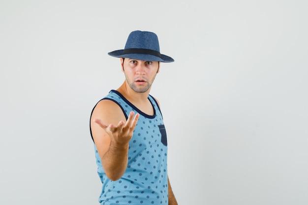 青い一重項、帽子、正面図で困惑したジェスチャーで手を伸ばす若い男。