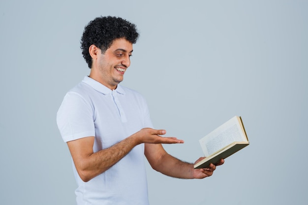 Young man stretching hand toward book in white t-shirt and jeans and looking happy. front view.