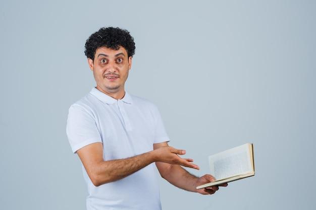 Giovane che allunga la mano verso il libro in maglietta e jeans bianchi e sembra felice. vista frontale.