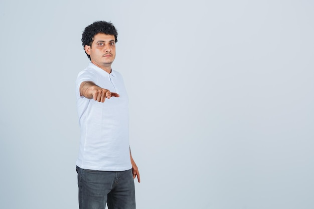 Giovane che allunga la mano verso la macchina fotografica in maglietta e jeans bianchi e sembra seria, vista frontale.