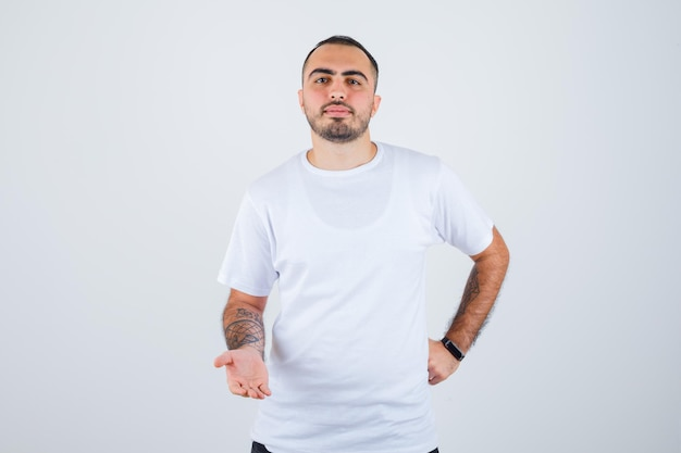 Young man stretching hands as holding something in white t-shirt and black pants and looking serious