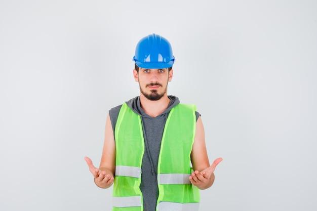 若い男は建設制服で疑わしい方法で手を伸ばして幸せそうに見えます