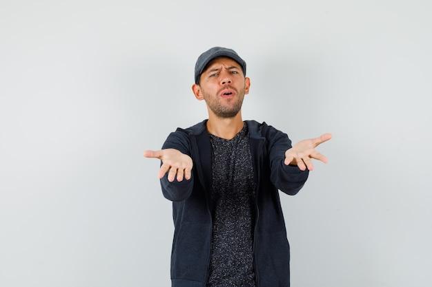 Молодой человек вопросительно протягивает руки в футболке, куртке, кепке