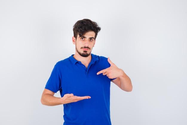 젊은 남자가 뭔가를 들고 파란색 티셔츠에 검지 손가락으로 가리키는 것으로 한 손을 뻗고 심각한 찾고