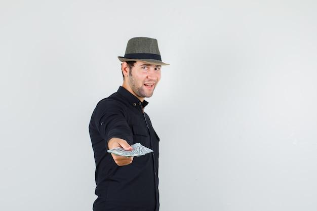 黒のシャツでドル札を伸ばす若い男