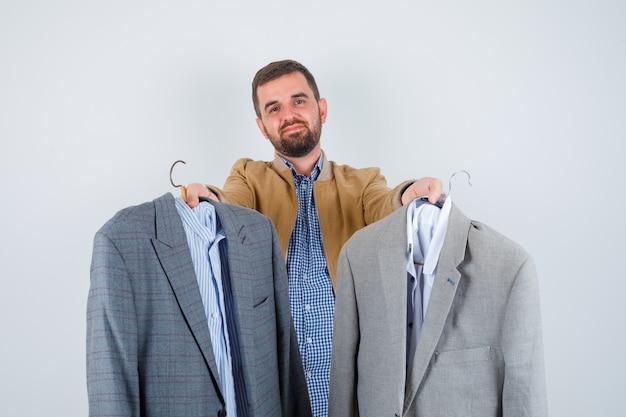 Молодой человек протягивает костюм к камере в куртке, рубашке и выглядит довольным, вид спереди.