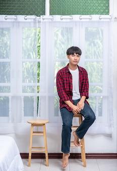 Un giovane con una camicia a righe è seduto su un seggiolone.