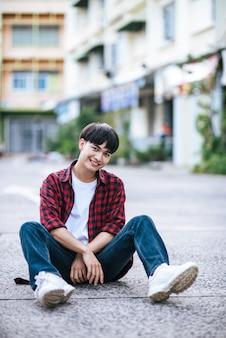 Un giovane con una camicia a righe seduto per strada