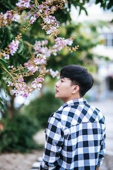 A young man in a striped shirt was standing on the roadside and holding the flower.