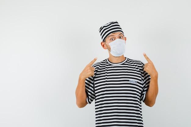 Giovane in cappello della maglietta a strisce che indica la sua mascherina medica