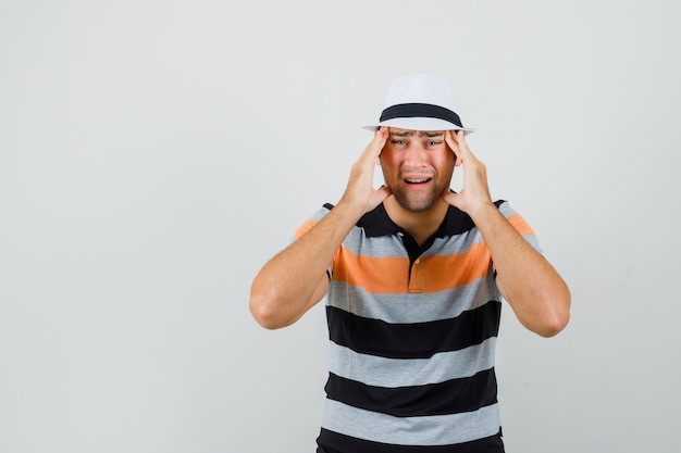 Giovane uomo in maglietta a righe, cappello che soffre di mal di testa e cerca spazio doloroso per il testo