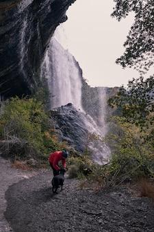 若い男がバックグラウンドで大きな滝で彼の犬のラブラドールをなでます。