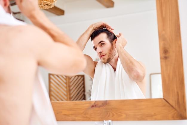 鏡のそばに立っている間彼の髪をなでる若い男