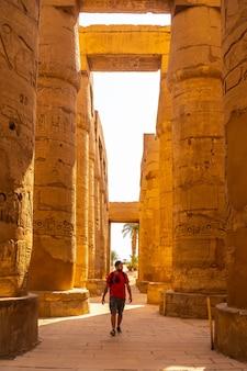 エジプト、カルナック神殿の象形文字の柱の間を散歩する若い男