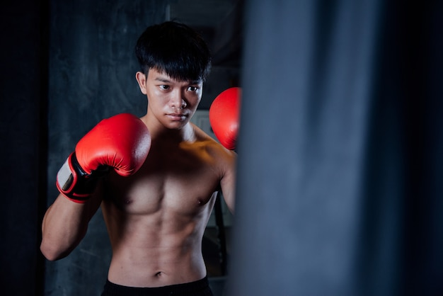 Young man strong sports man boxer make exercises in gym, healthy concept