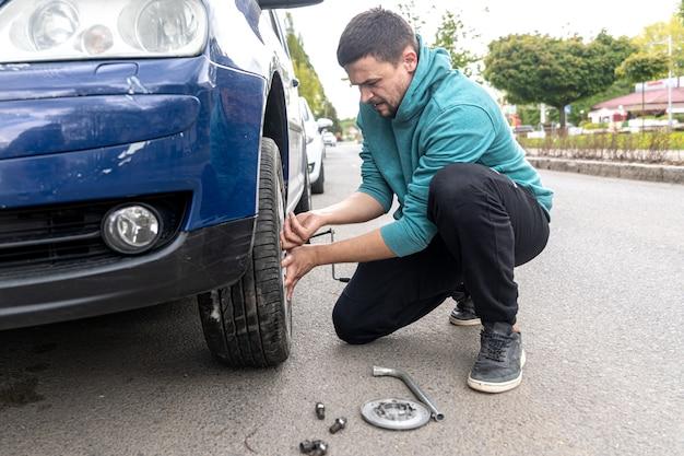 ナットを緩めるためにホイールスパナと戦うときに、車のタイヤを交換するのに苦労している若い男。