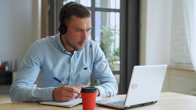 若い男の学生は、ラップトップを使用して自宅で勉強し、オンラインで学習します。