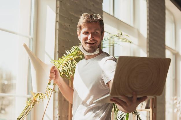 정원사, 생물 학자, 꽃집에 대한 온라인 과정에서 집에서 공부하는 젊은 남자. 노트북 사용