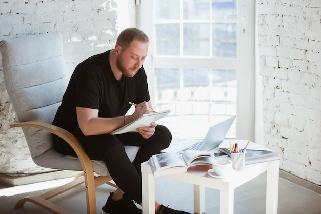 Молодой человек учится дома во время онлайн-курсов для учителя, менеджера медицинской службы