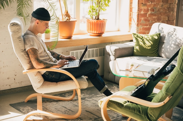 Молодой человек учится дома во время онлайн-курсов или бесплатной информации сам