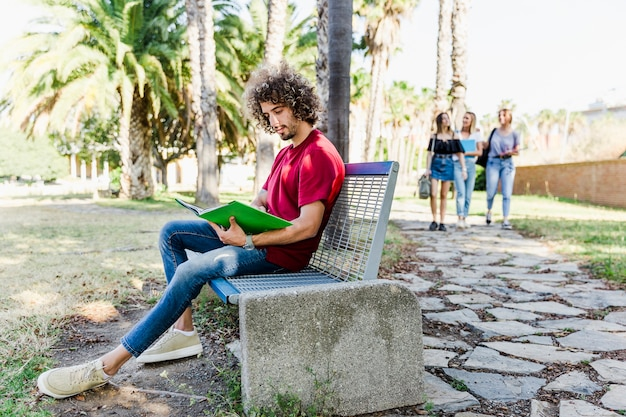 Young man studying on bench
