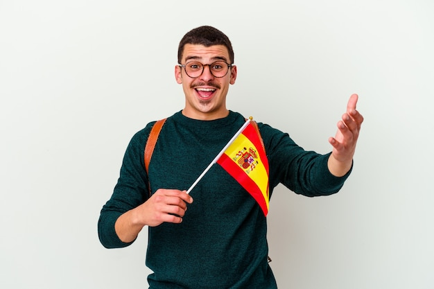 Young man studying english isolated on white wall receiving a pleasant surprise, excited and raising hands