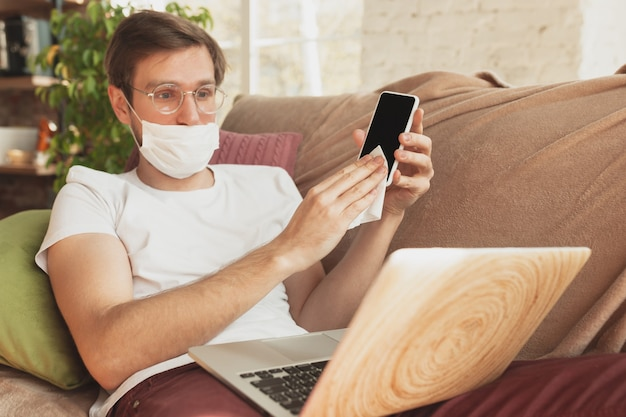 Young man studying at home during online courses for disinfector, nurse, medical services.
