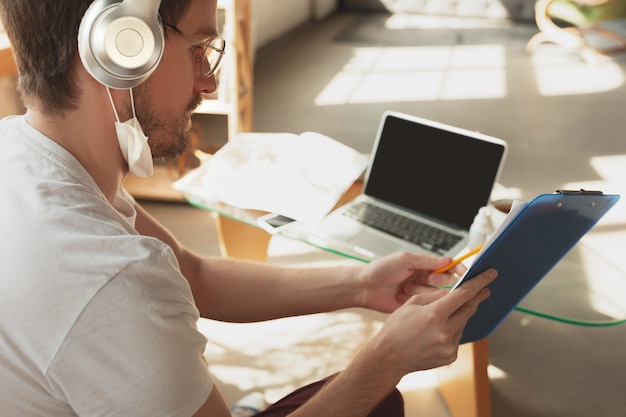 Young man studying at home during online courses for laborer, journalist, developer. using laptop, smartphone, headphones.