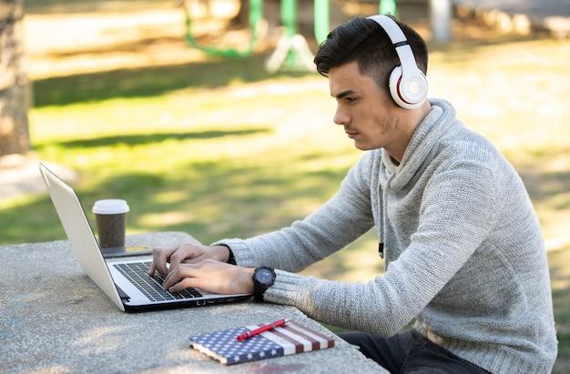 Молодой человек учится с компьютером, слушая музыку в наушниках в парке без маски