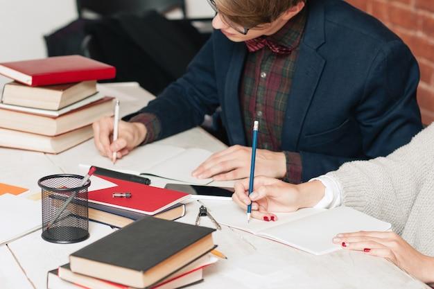 図書館で女の子と一緒に勉強している若い男。図書館ですり減る学生のペアの職場。