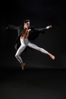 Young man in stylish clothes jumping and dancing on black background