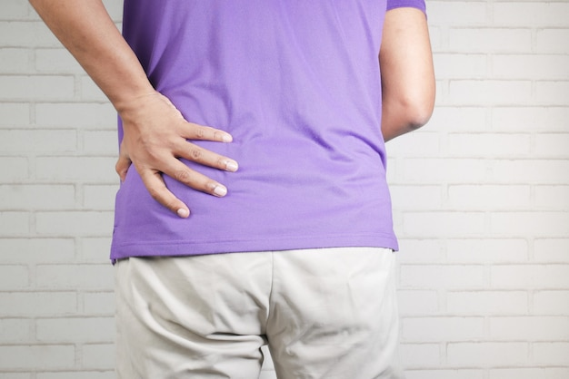 Young man suffering back pain close up