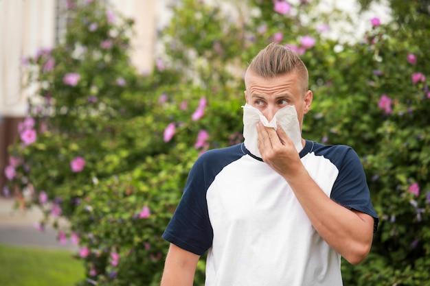 야외에서 알레르기로 고통받는 젊은 남자