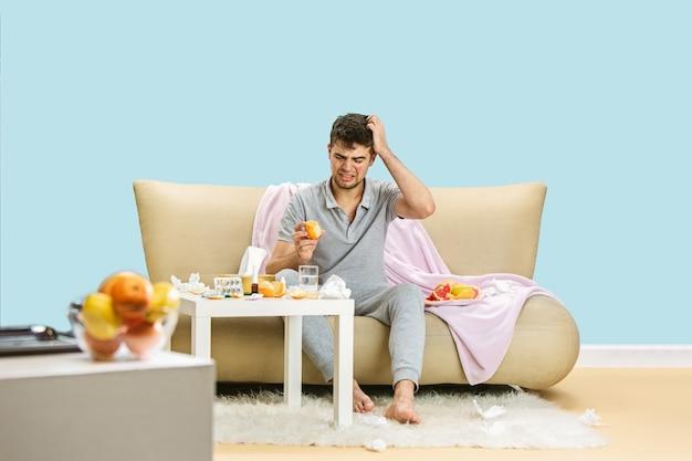 柑橘系の果物に対するアレルギーに苦しんでいる若い男。皮膚の発疹、かゆみ、ナプキンのくしゃみ、グレープフルーツとオレンジに囲まれて座っている。結果のない薬を服用している。ヘルスケアの概念。