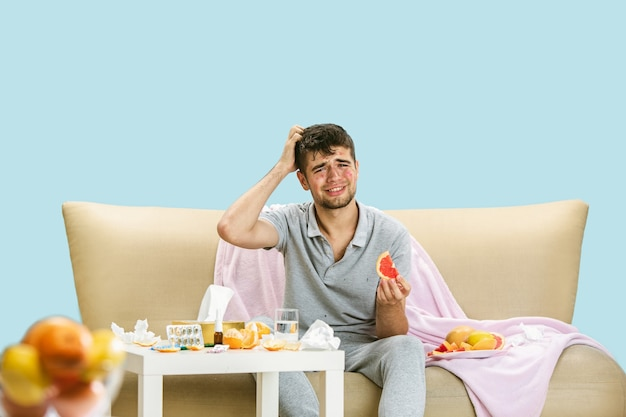 柑橘系の果物に対するアレルギーに苦しんでいる若い男。皮膚の発疹、かゆみ、ナプキンのくしゃみ、グレープフルーツとオレンジに囲まれて座っている。薬を飲んでも結果はありません。ヘルスケアの概念。