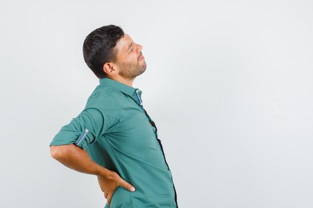 シャツの背中の痛みに苦しんでいる若い男。