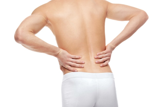 Young man suffering from back pain on white