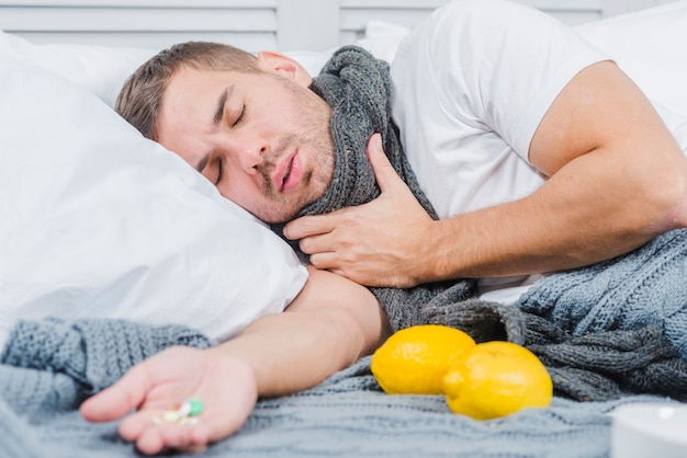Young man suffering from cold lying on bed with pills in his hand