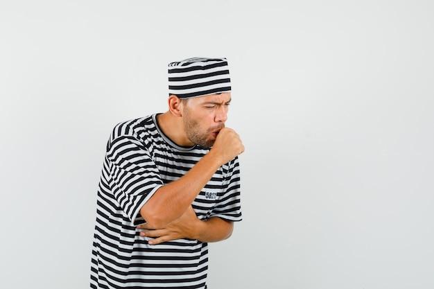 Giovane che soffre di tosse in maglietta a righe, cappello e sembra malato.