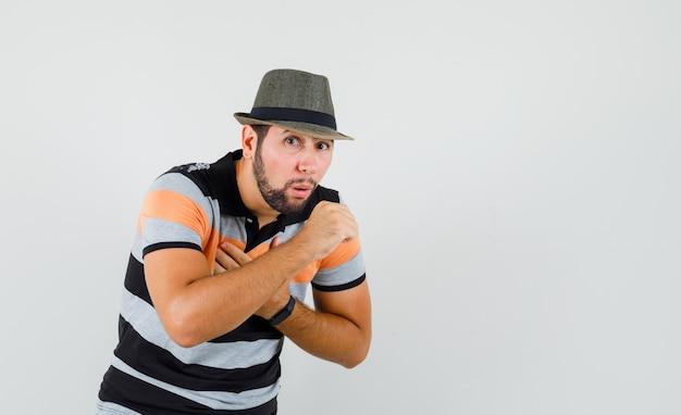 Giovane che soffre di tosse in maglietta, cappello e sembra malato