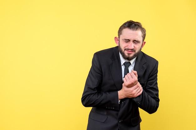 Молодой человек страдает от боли в руке, стоя над желтым