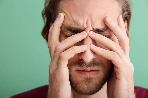 色の頭痛に苦しんでいる若い男