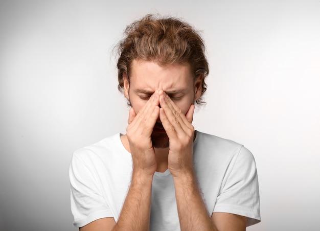 Молодой человек страдает от головной боли на светлой поверхности